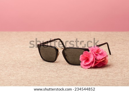 brown Sunglasses on canvas background an pink flower - stock photo