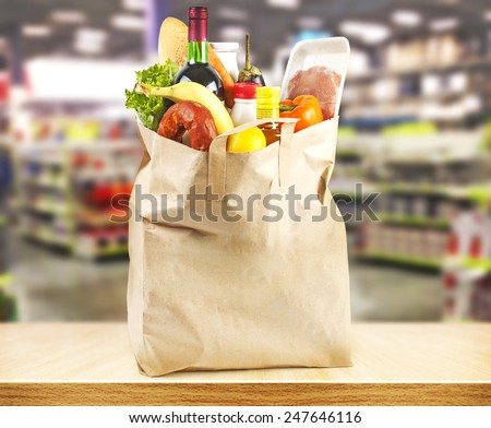 Brown table and on background blured supermarket and bag with products - stock photo