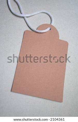 Brown tag with white string on grey card board