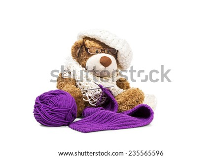 Brown teddy bear in a knitted beret knitting needles scarf isolated on white background - stock photo