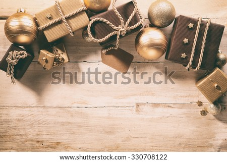 Brown themed festive Christmas border with golden Xmas baubles and decorative gifts on a wooden boards with copyspace for your seasonal greeting, overhead view - stock photo