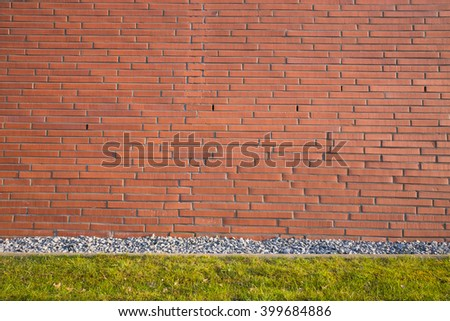 brown tone brick wall texture background with a stone and green garden