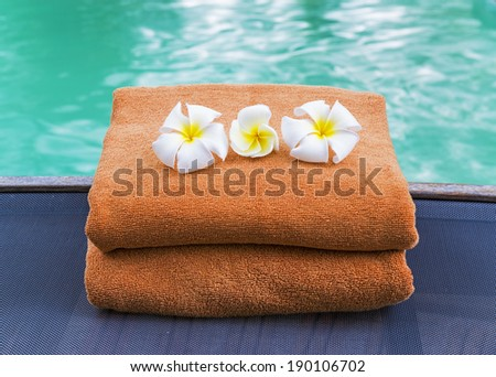 Brown towels and frangipani at swimming pool  - stock photo