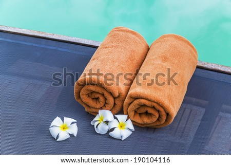 Brown towels and frangipani on pool chairs at swimming pool  - stock photo