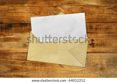Brown Vintage Envelope with blank paper on wood . - stock photo