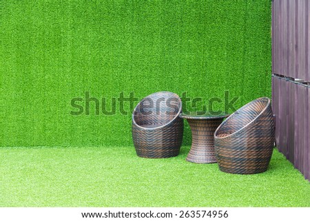 Brown wicker chair on the green background - stock photo