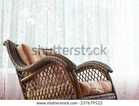 Brown wicker rocking chair against the window's curtains, indoor composition - stock photo