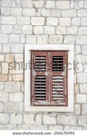 Brown window with shutters in old stone house, Croatia - stock photo