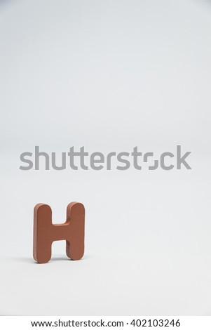 Brown Wooden alphabet H with white background in Vertical view - stock photo