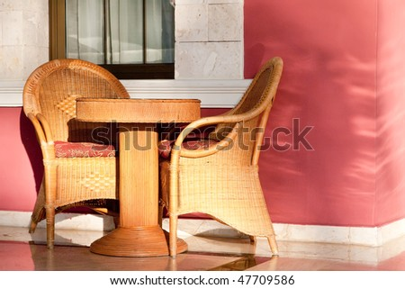 Brown wooden chairs an tables on patio in the morning