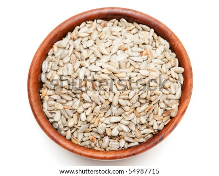 Brown wooden cup with cleaned seed on white background