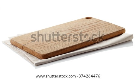 Brown wooden cutting board on cotton napkin isolated on white background. Clipping path - stock photo