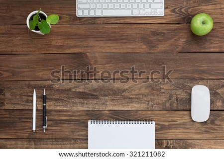 Brown Wooden Desk with Stationery Electronics Flora and Food Natural Wood Background Small Green Plant and Apple Computer Mouse and Keyboard Black and White Pens Blank Notepad Top View - stock photo