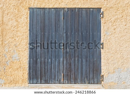 brown wooden door in a yellow wall - stock photo