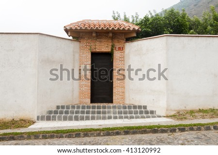Brown wooden door on brick wal - stock photo