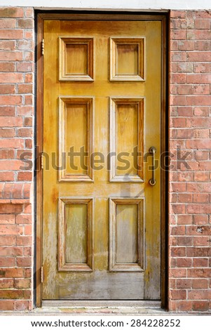 Brown wooden door on brick wall