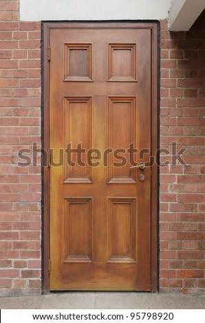 Brown wooden door on brick wall - stock photo