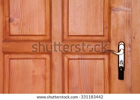 brown wooden door with handle and key in keyhole closeup - stock photo