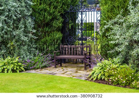 Brown wooden garden bench in the old Victorian garden - stock photo