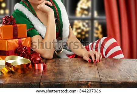 brown wooden table and free space and elf in green dress  - stock photo