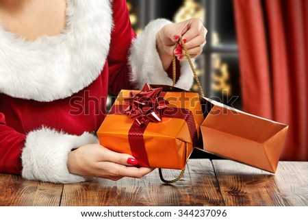 brown wooden table and gift in hands and bag  - stock photo