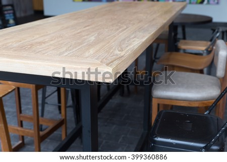 brown wooden table with stool at patio of building