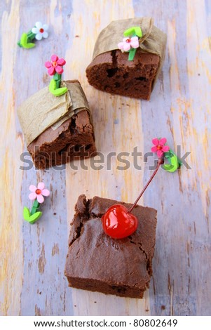 brownie chocolate cakes with cherries on a brown background