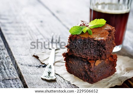 brownie on a dark wood background. tinting. selective focus on mint - stock photo