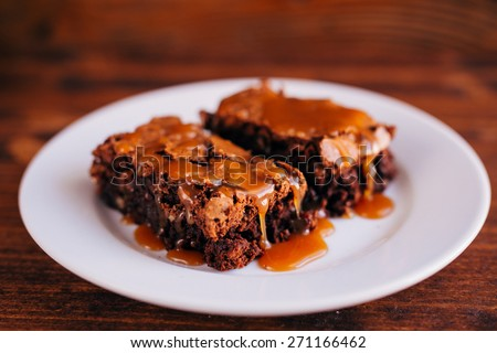 Brownies with nuts and salted caramel. Chocolate cake with nuts and caramel. Brownies on a plate sprinkled with caramel. Stretching caramel on the cake - stock photo