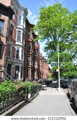 Brownstone Homes New York Urban Residential Neighborhood Sidewalk Sunny Blue Sky Day - stock photo