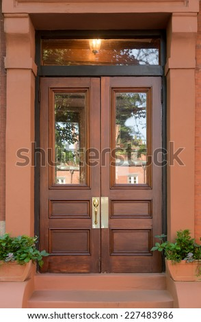 Brownstone Portico with Double Natural Wooden Front Doors with Potted Plants