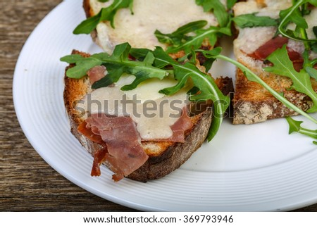 Bruchetta with prosciutto, parmesan and fresh ruccola - stock photo