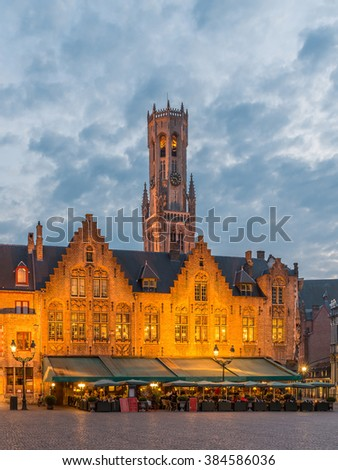 Bruges, Famous Scenic skyline with the picturesque night medieval belfry of Bruges (Belfort van Brugge) at Burg Square Illuminated cityscape under dramatic sky in Summer, Belgium - stock photo