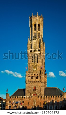 BRUGGE, BELGIUM - 9 MAY: Ancient medieval tower with clock in Brugge, Belgium on 9 MAY 2013.The belfry of Bruges, or Belfort, is a medieval bell tower in the historical centre of Bruges.