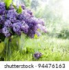 Brunch of lilacs in bucket against the backdrop of green garden - stock photo