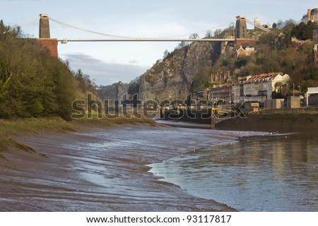 Brunel's landmark Clifton suspension bridge over the River Avon, Bristol at low tide in midwinter - stock photo