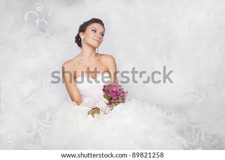 Brunet bride portrait with flowers in studio - stock photo