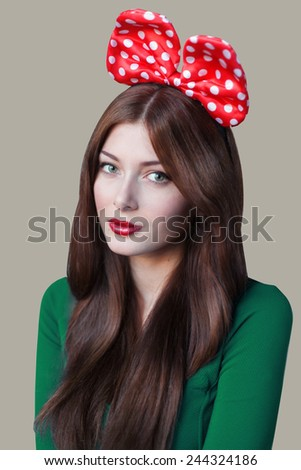 Brunet cheerful young woman with red  bow in green dress. Beauty portrait, perfect makeup. Valentine's Day. Long chic elegant hair. - stock photo