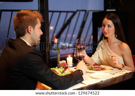 Brunette and young guy met at a restaurant for dinner - stock photo