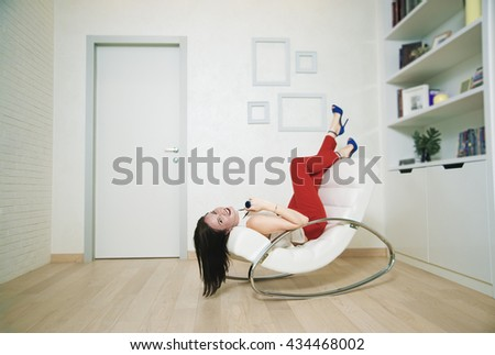 brunette asian Woman relaxing in armchair near door and white wall, looking at camera, smiling, smiley face. young adult girl wear red trousers and blue high heel - stock photo