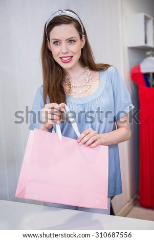 Brunette at till with shopping bag in fashion boutique