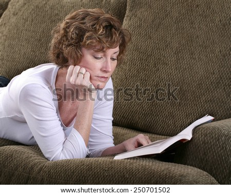 Brunette attractive woman reading a book relaxing on a couch