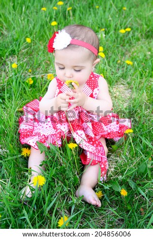 Brunette baby girl sitting in a field with dandelions - stock photo