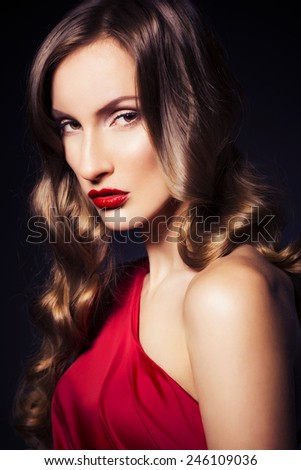 Brunette beautiful luxury woman in red dress with clear skin and evening dark make up: green cat eye and brown eyeshadows. Waved hairstyle. Dark background