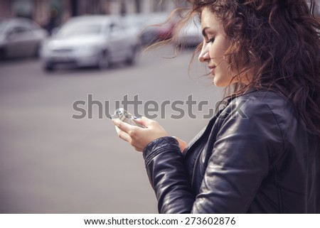 Brunette beautiful stylish caucasian woman in casual outfit on a walk on european city street typing message on her phone. copy space - stock photo