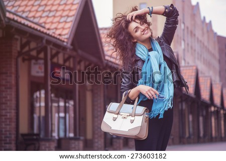 Brunette beautiful stylish caucasian woman in casual outfit on a walk on european city street. copy space