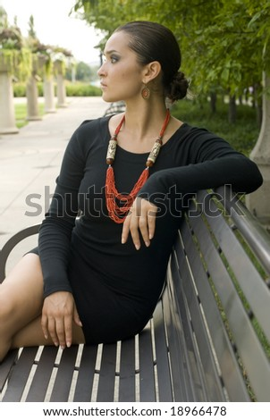 Brunette beauty in black dress sitting on park bench on a sunny day - stock photo