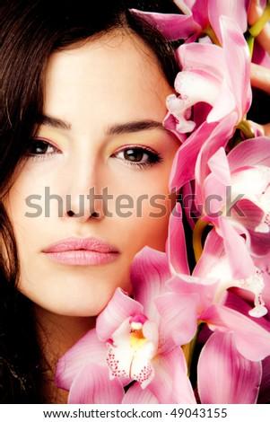 brunette beauty portrait with pink orchid, studio shot - stock photo