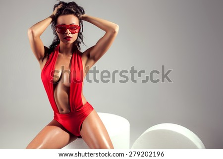 Brunette beauty posing in sexy red lingerie and fashionable sunglasses. Girl with perfect slim body . Studio shot. - stock photo