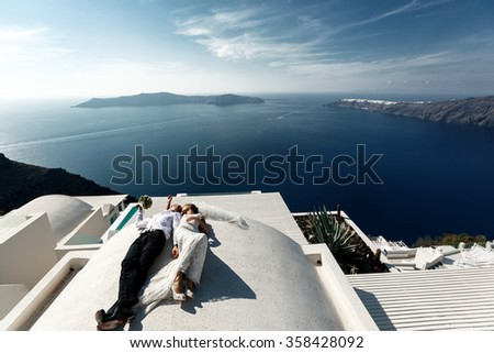 Brunette bride and groom lying on the terrace in white dress with sea background